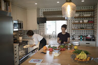 Mother and daughter cooking, preparing pizza and salad in kitchen - HEROF10516