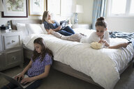 Mother and daughters relaxing, reading magazine, watching TV and using laptop in bedroom - HEROF10525