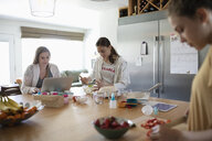 Mother and daughters using laptop and baking in kitchen - HEROF10531