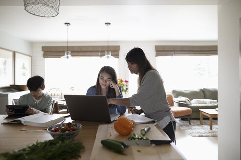 Mother cooking and helping tween daughter at laptop in kitchen - HEROF10543