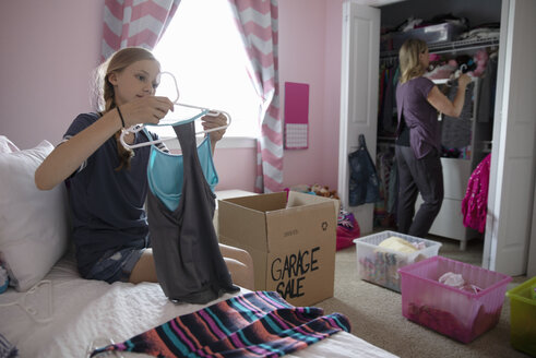 Mother and daughter organizing bedroom closet, donating clothes - HEROF10558