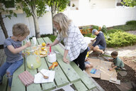 Mother and son making lemonade on patio - HEROF10582