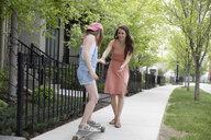 Mother helping daughter skateboarding on neighborhood sidewalk - HEROF10588