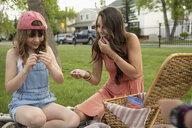 Mother and daughter eating, enjoying picnic in park - HEROF10591