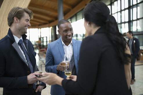 Business people drinking champagne, networking at conference - HEROF10649