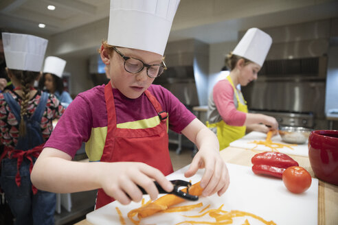 Focused boy shredding carrots in cooking class - HEROF10670