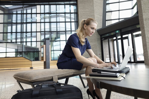 Businesswoman working at laptop in office lobby - HEROF10682