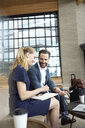 Smiling businessman and businesswoman working in lobby - HEROF10697