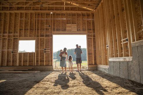Family standing in sunny, rural barn under construction - HEROF10751