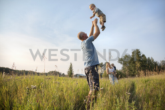 Playful father throwing baby son overhead in sunny, rural field - HEROF10763 - Hero Images/Westend61