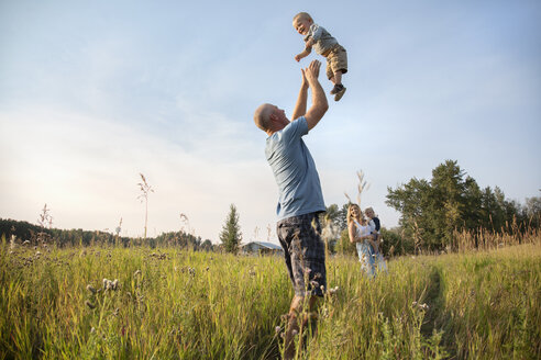 Playful father throwing baby son overhead in sunny, rural field - HEROF10763