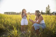 Mother and daughter in sunny, rural field - HEROF10769
