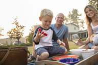 Playful boy with raspberries on fingers enjoying picnic with parents - HEROF10775