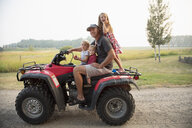 Portrait father and young children riding quadbike on farm - HEROF10778