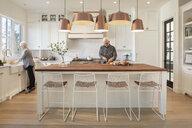 Senior couple cooking in modern kitchen - HEROF10802