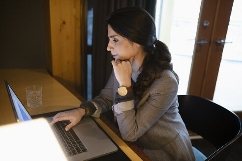 Focused businesswoman working at laptop - HEROF10817