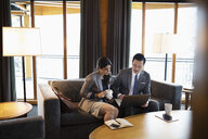 Business people meeting, drinking coffee and using laptop in hotel lobby - HEROF10823