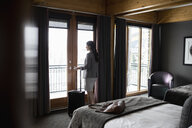 Thoughtful businesswoman looking out hotel room window - HEROF10832