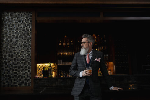 Fashionable hipster businessman with beard drinking cocktail in bar - HEROF10892