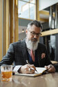 Fashionable hipster businessman with beard writing in notebook in bar - HEROF10895