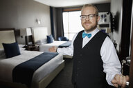Portrait friendly male hotel bellhop opening hotel room door - HEROF10922