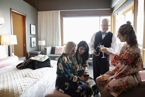 Room service hotel staff pouring champagne for women friends enjoying spa weekend in hotel room - HEROF10934