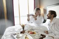 Happy couple in bathrobes eating breakfast in bed in hotel room, enjoying romantic weekend - HEROF10958