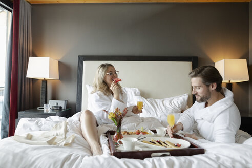 Couple in bathrobes enjoying breakfast in bed in luxury hotel, enjoying romantic weekend - HEROF10961