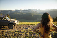 Woman looking at sunny mountain view near SUV, Alberta, Canada - HEROF11063