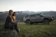 Women friends drinking coffee near SUV in mountain field, Alberta, Canada - HEROF11066