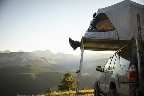 Womans feet dangling from SUV rooftop tent in idyllic mountain field, Alberta, Canada - HEROF11072