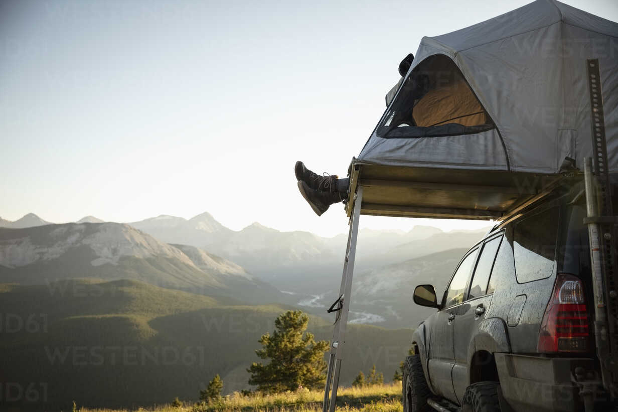 Womans feet dangling from SUV rooftop tent in idyllic mountain field, Alberta, Canada - HEROF11072 - Hero Images/Westend61