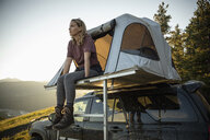 Woman relaxing at SUV rooftop tent - HEROF11075