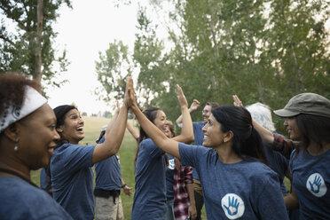 Volunteers high-fiving in park - HEROF11099