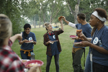 Volunteers eating pizza in park - HEROF11102