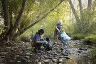 Women volunteering, cleaning up garbage in stream - HEROF11105