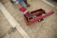 Woman reaching into toolbox at construction site - HEROF11114