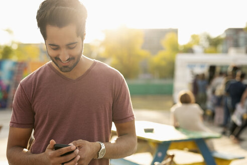 Young man texting with smart phone in sunny park - HEROF11171