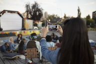 Woman using smart phone at movie in the park - HEROF11174