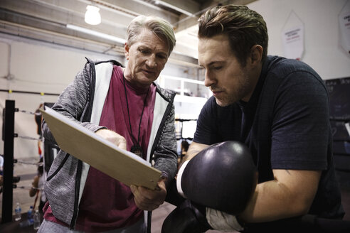 Trainer with clipboard talking to male boxer in gym - HEROF11246