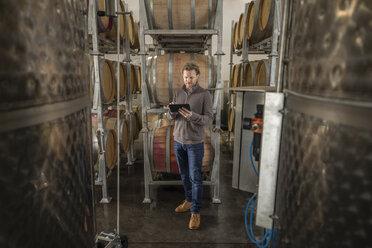 Winemaker with digital tablet examining wine casks in vineyard - HEROF11258