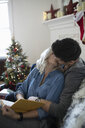 Affectionate young couple kissing, reading book in Christmas living room - HEROF11279