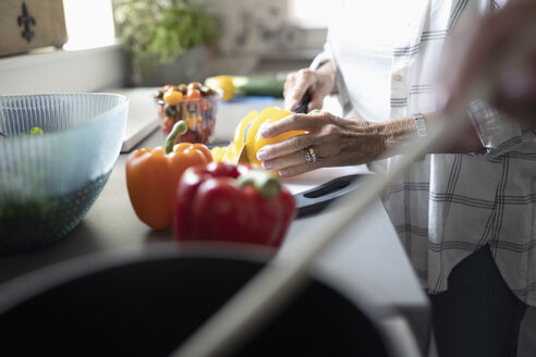 Close up senior woman cutting bell peppers, cooking in kitchen - HEROF11291
