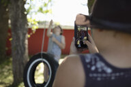 Boy with camera phone photographing brother playing on tire swing - HEROF11318