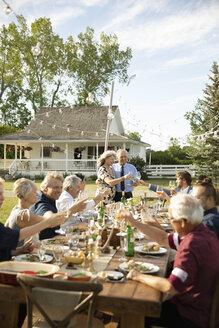 Affectionate couple celebrating anniversary, toasting friends at garden party table - HEROF11330