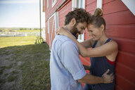 Affectionate couple hugging at red barn on rural farm - HEROF11339