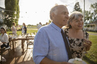 Affectionate couple eating cake and drinking wine, celebrating anniversary at sunny, rural garden party - HEROF11345