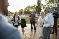 Affectionate senior couple dancing at wedding reception in rural garden - HEROF11351