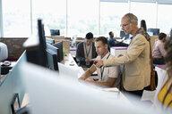 Businessmen working at computer in open plan office - HEROF11408