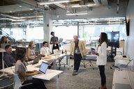 Businesswoman leading meeting in open plan office - HEROF11423